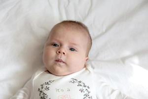 portret van een babymeisje dat in bed ligt foto