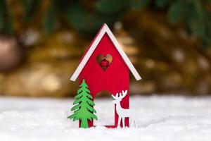 kerst houten speelgoed huis herten en boom op een witte deken die sneeuw imiteert foto
