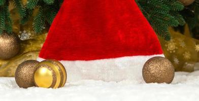 kerstmuts op de achtergrond van een kerstboom en slingers foto