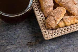 croissants liggen in een rieten mand met theekop foto
