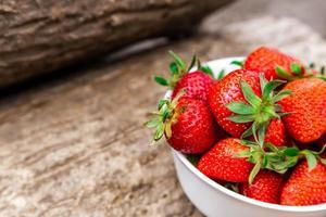 kom vol met verse aardbeien op bruine tafel foto