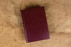 een stapel oude boeken over een jutetextuur foto