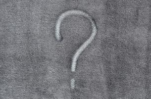 vraagteken op de grijze achtergrond van de stoffentextuur foto