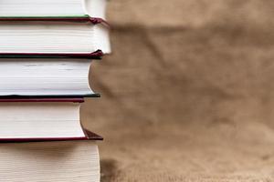 een stapel of gebonden oude boeken op een jutetextuur met plaats voor tekst foto
