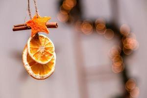 hangende kerstversiering van gedroogde sinaasappels, mandarijn en kaneelsterren met kopie ruimte voor tekst foto