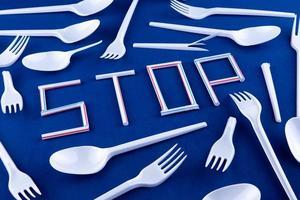 het woord stop gemaakt van plastic buizen op een blauwe achtergrond met plastic keukengerei foto