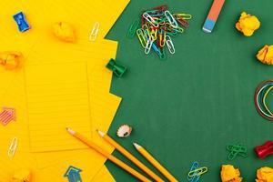schoolbenodigdheden en oranje vel papier op het groene schoolbestuur foto