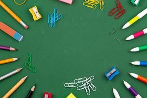 schoolbenodigdheden liggen op een groen schoolbord foto