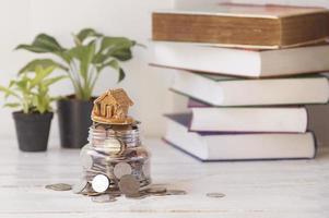 huis met munten plant en boek achtergrond op tafel concept bij het kopen van lening en het verkopen van huis foto