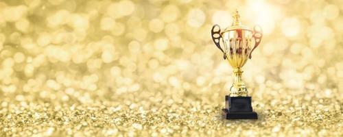 1e kampioen kent de beste prijs en winnaar conceptkampioenschapsbeker of winnaarstrofee toe op gouden vloer met bokehachtergrond foto