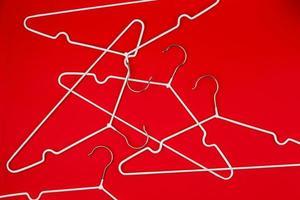 witte kleerhangers op rode achtergrond foto