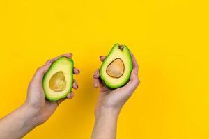 avocado in een vrouwelijke hand is geïsoleerd op een gele achtergrond foto
