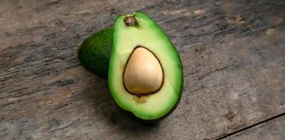 verse avocado in tweeën gesneden op een houten bord achtergrond foto