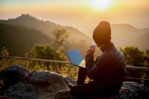 reiziger drinkt 's ochtends koffie met uitzicht op het berglandschap foto