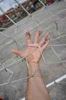 hand aanraken van een touwnet foto