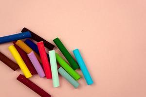 kleurrijke kleurpotloden pastelkleuren verscheidenheid van gekleurd krijt plat lag op roze foto