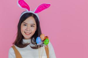portret van mooi Aziatisch meisje met een paasei op een roze achtergrond kopie ruimte foto