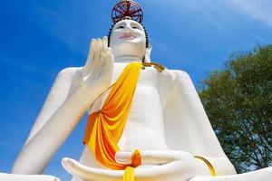 groot wit Boeddhabeeld op een blauwe hemelachtergrond foto