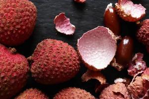 fotografie van litchis hele schil en zaden op leisteen achtergrond voor voedsel illustratie foto