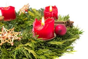 versierde komstkrans gemaakt van dennentakken met brandende rode kaarsen foto