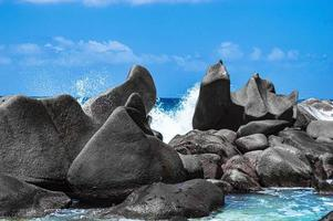 golven breken op eeuwenoude granieten blokken foto