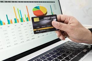 Aziatische accountant werken berekenen en analyseren rapport projectboekhouding met notebook en creditcard in moderne kantoor financiën en business concept foto
