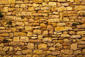 oude muur van stenen en mortel met bakstenen foto