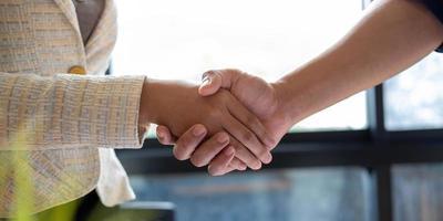 close-up van mensen uit het bedrijfsleven handen schudden afwerking vergadering zakelijke etiquette felicitatie fusie foto