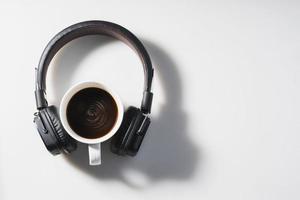 hoofdtelefoons en koffiekopje op witte achtergrond foto