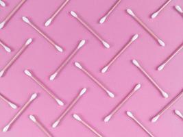 patroon gemaakt van bamboe wattenstaafjes op roze achtergrond foto