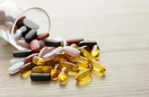 visolie capsules en multivitamine supplementen uit het kleine glas op de houten tafel met kopie ruimte foto