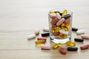 visolie capsules en multivitamine supplementen in het kleine glas op de houten tafel met kopie ruimte foto