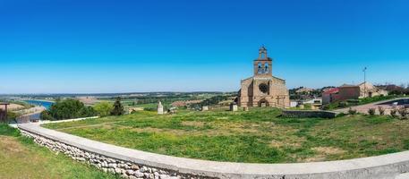 panoramisch van een stenen kerk in castiliaans dorp in spanje foto