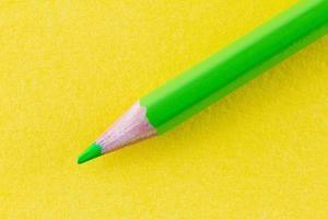 groen kleurpotlood op geel kleurendocument diagonaal gerangschikt foto