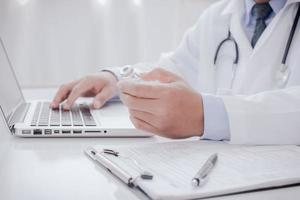 arts doet papierwerk en gebruikt laptop in kliniekbeschrijving in een servercomputer in ziekenhuisconcept bedacht een genezingsvaccin voor coronavirusziekte covid19 foto