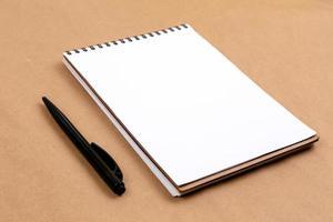 plat lag bovenaanzicht foto van een potlood en een notitieblok op een beige achtergrond