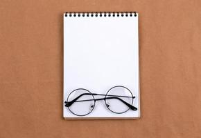 plat lag bovenaanzicht foto van bril en blocnote op een beige abstracte achtergrond met kopie ruimte minimale stijl