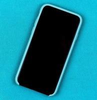 smartphone in aqua blauw hoesje op een trendy aquaachtergrond met ruimte voor tekst foto