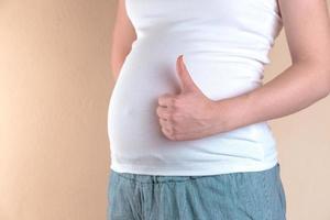 een close-up van de buik van een zwangere vrouw die een soortgelijk teken vertoont foto
