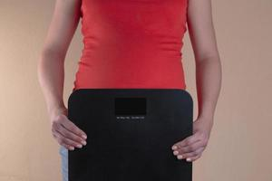 een close-up van de buik van een zwangere vrouw in het rood die een weegschaal in haar handen houdt foto