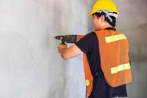de monteur boort de betonnen muur foto