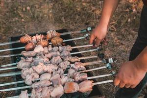 man frituren shish kebab op de grill foto