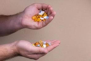een stapel multi gekleurde pillen in mannelijke handen foto