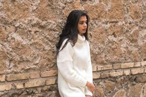 jonge contemplatieve brunette vrouw leunend tegen een bakstenen muur foto