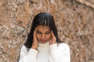 close-up portret van een vermoeide brunette vrouw die haar slapen wrijft en masseert om een vreselijke hoofdpijn te verlichten foto