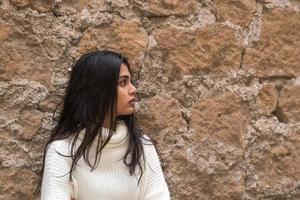 profiel portret van een jonge romantische brunette vrouw leunend tegen een bakstenen muur foto