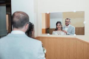 bruid en bruidegom omhelzen elkaar en kijken in hun spiegelbeeld in de spiegel foto