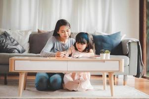 Aziatische moeder en dochter studeren samen foto