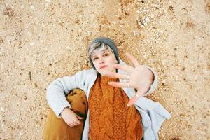 een avonturier jonge blanke vrouw liggend op zandgrond naast een rugzak met wollen trui en pet met haar hand open en de sinaasappel als hoofdkleur foto