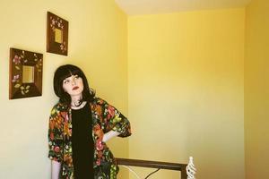 mooie brunette vrouw in een gele kamer in haar huis foto